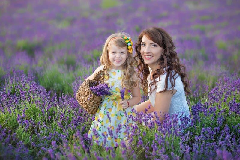 Madre joven con la hija joven que sonríe en el campo de la lavanda Hija que se sienta en las manos de la madre Muchacha en colori fotografía de archivo
