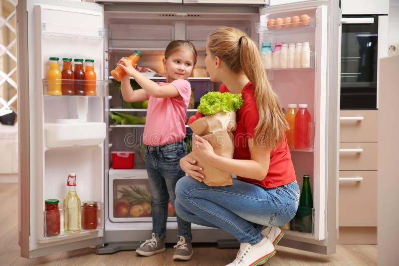 Madre joven con la hija que pone la comida en el refrigerador foto de archivo