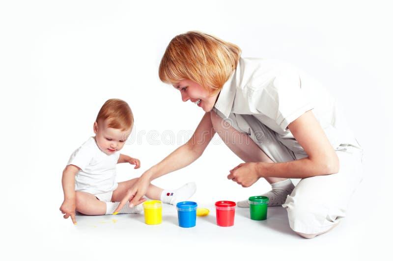 Madre joven con la pintura bonita del bebé fotografía de archivo libre de regalías