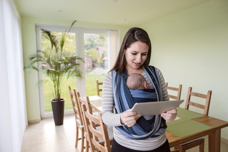 Madre joven con su hijo en la honda, sosteniendo la tableta foto de archivo libre de regalías