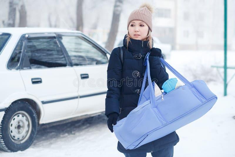 Madre joven con su niño del bebé en el bolso de la cuna al aire libre en el invierno imagen de archivo libre de regalías