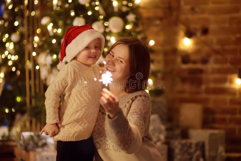 Madre joven con su pequeña Navidad de la celebración del hijo con la bengala en sala de estar acogedora en invierno foto de archivo