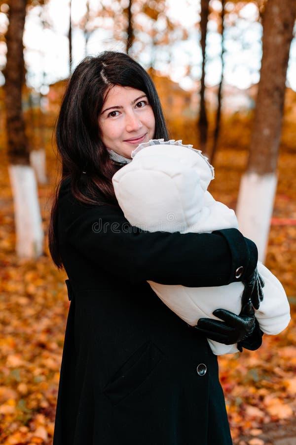 Madre joven con su pequeño bebé a mano en parque del otoño fotografía de archivo