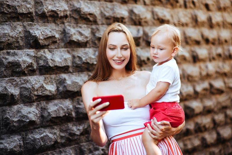 Madre joven con su pequeño hijo en la ciudad fotos de archivo libres de regalías