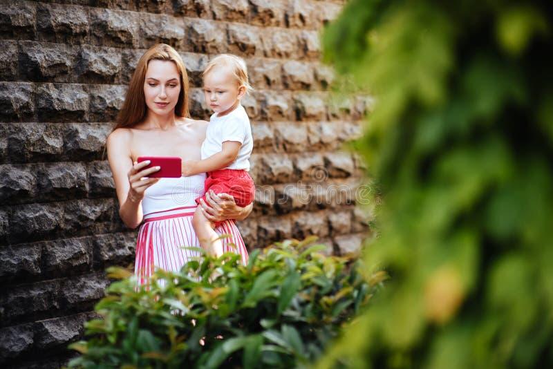 Madre joven con su pequeño hijo en la ciudad fotografía de archivo