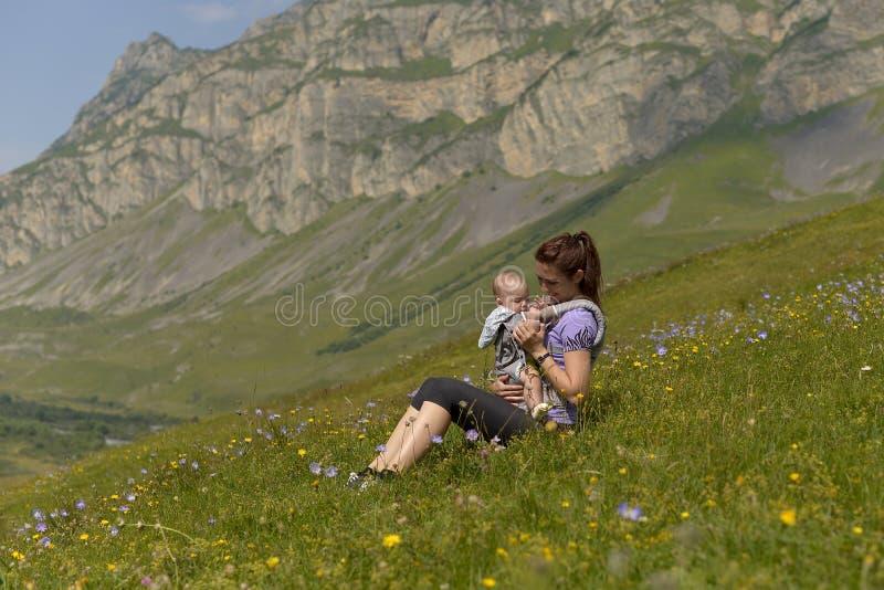 Madre joven con un pequeño niño en viajes mochila-que llevan en las montañas fotografía de archivo