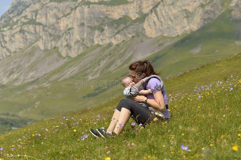 Madre joven con un pequeño niño en viajes mochila-que llevan en las montañas fotos de archivo libres de regalías