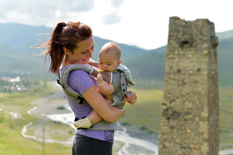 Madre joven con un pequeño niño en viajes mochila-que llevan en las montañas foto de archivo libre de regalías