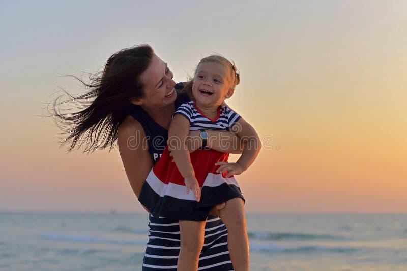 Madre joven con una pequeña hija que juega en la playa fotografía de archivo