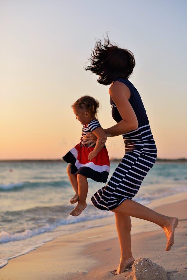 Madre joven con una pequeña hija que juega en la playa foto de archivo