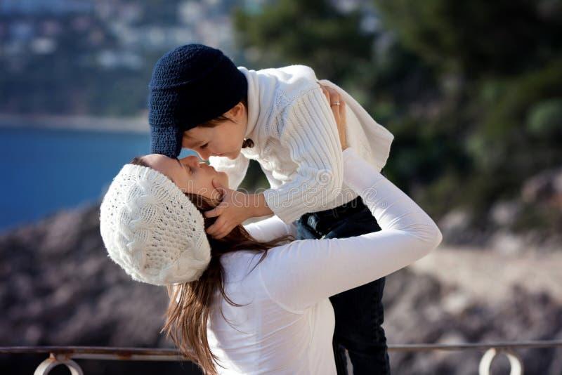 Madre joven, dando un beso a su niño pequeño imagen de archivo libre de regalías