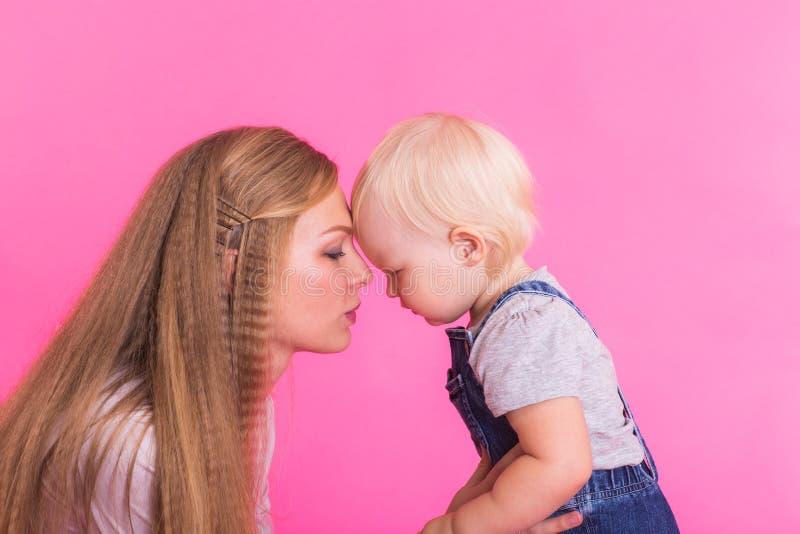 Madre joven e hija que se divierten junto en fondo rosado foto de archivo libre de regalías