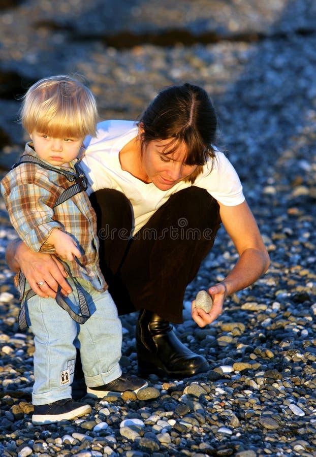 Madre joven e hijo que juegan en la playa en la puesta del sol imágenes de archivo libres de regalías