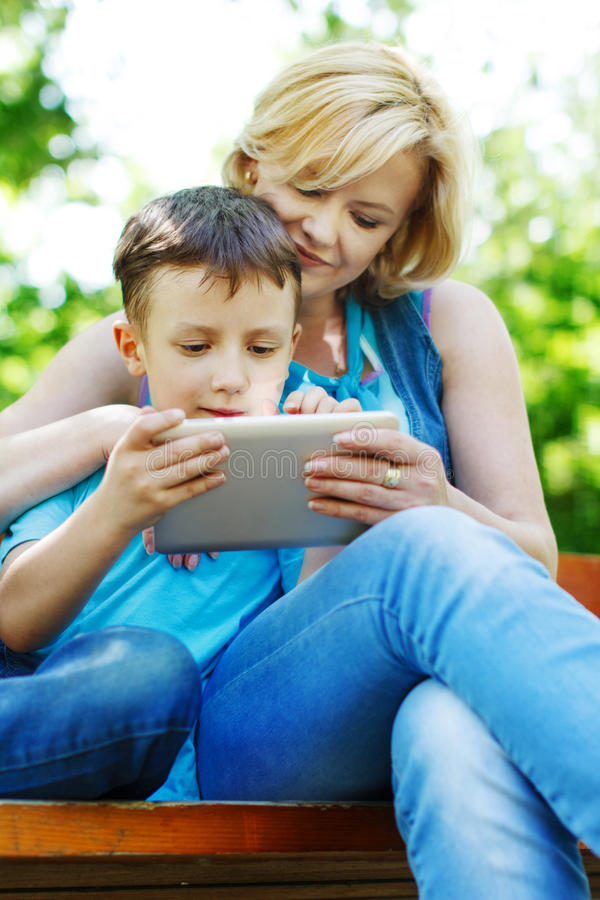 Madre joven e hijo que juegan en la tableta foto de archivo