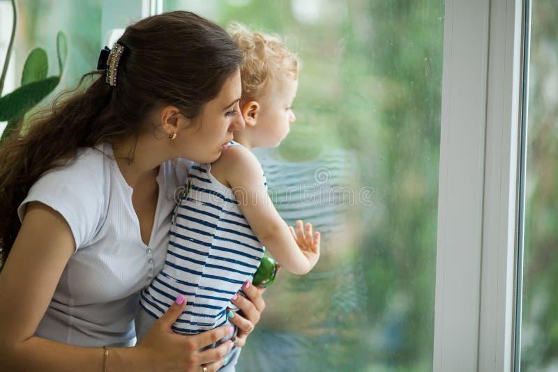 Madre joven e hijo que miran la lluvia a través de la ventana foto de archivo