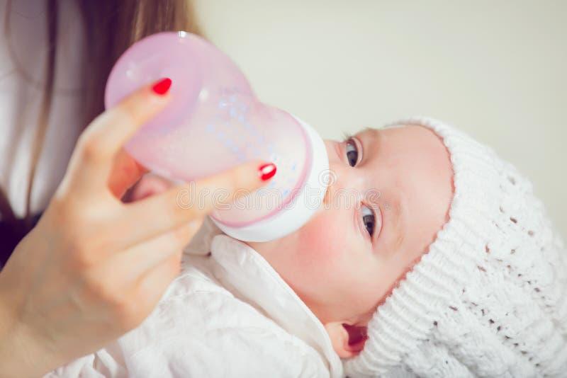 Madre joven en casa que alimenta a su nuevo bebé foto de archivo libre de regalías