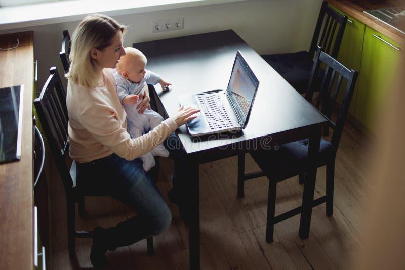Madre joven en Ministerio del Interior con el ordenador y su bebé Freelancer o blogger, trabajo y cuidado de niños foto de archivo