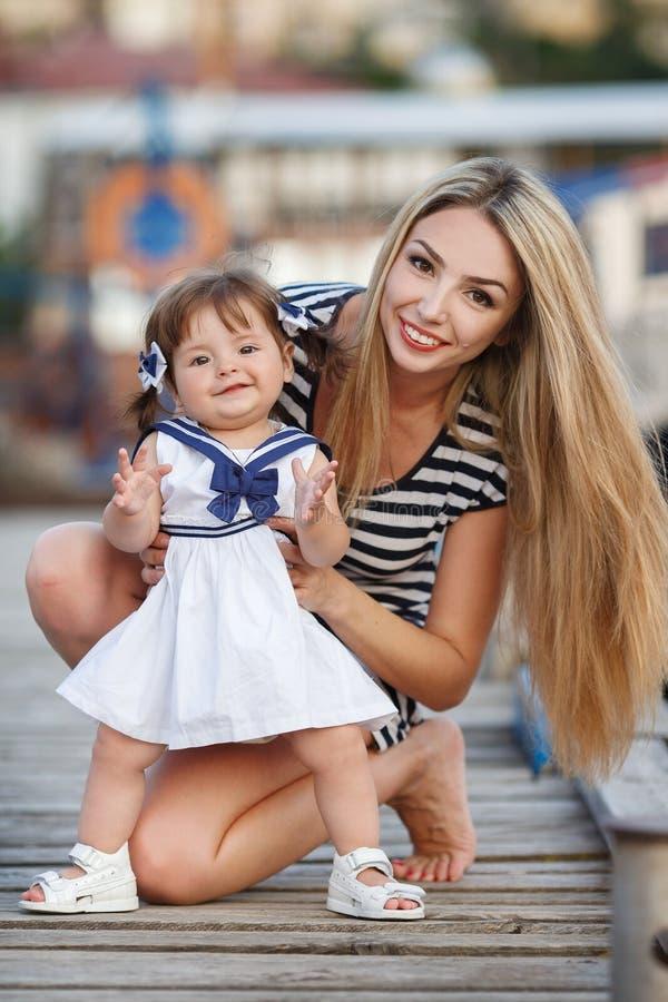 Madre joven feliz con una hija joven cerca del club náutico fotografía de archivo libre de regalías