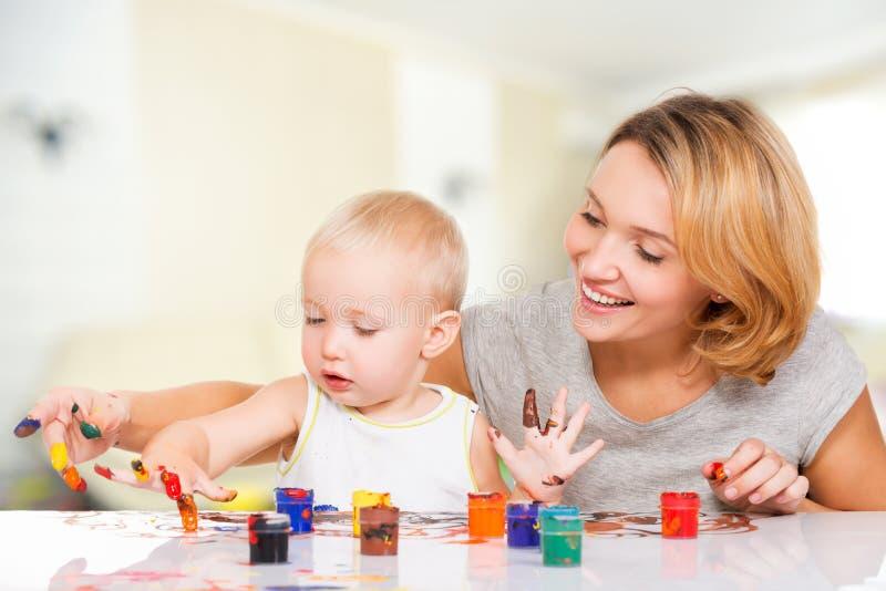 Madre joven feliz con una pintura del bebé por las manos. imagen de archivo