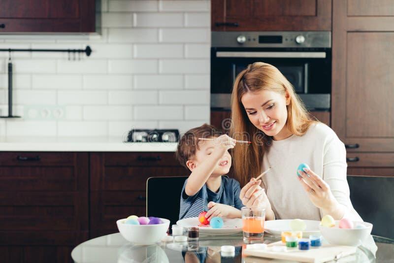 Madre joven feliz de Pascua y su pequeño hijo que pintan los huevos de Pascua imagen de archivo libre de regalías