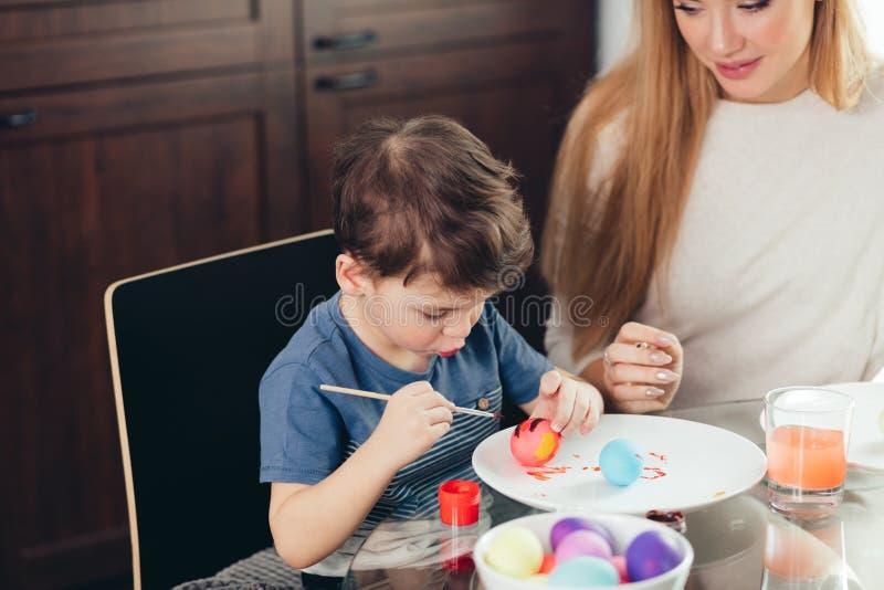Madre joven feliz de Pascua y su pequeño hijo que pintan los huevos de Pascua imagenes de archivo
