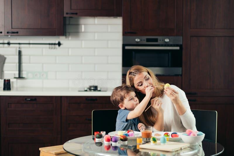 Madre joven feliz de Pascua y su pequeño hijo que pintan los huevos de Pascua fotos de archivo