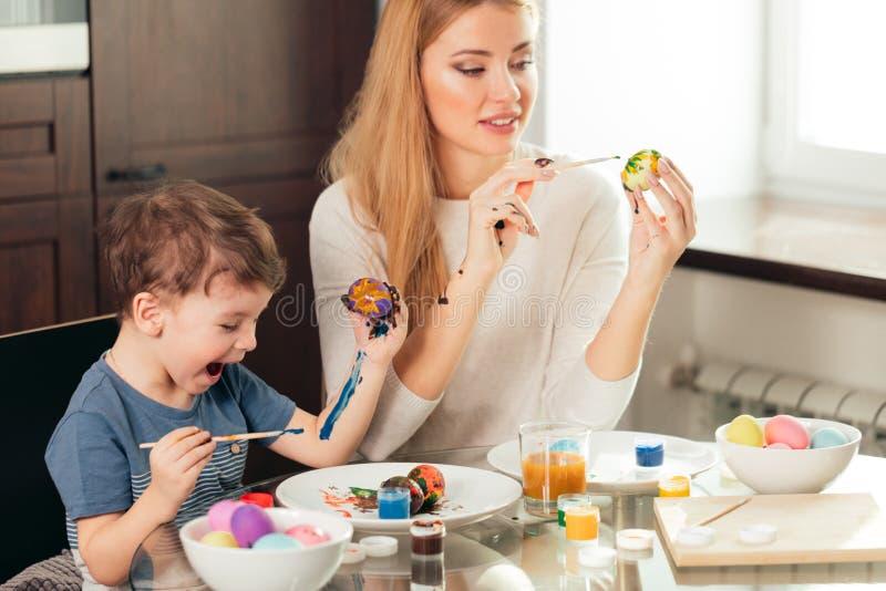 Madre joven feliz de Pascua y su pequeño hijo que pintan los huevos de Pascua fotografía de archivo