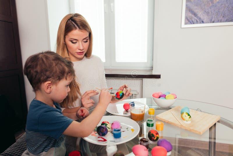 Madre joven feliz de Pascua y su pequeño hijo que pintan los huevos de Pascua foto de archivo libre de regalías