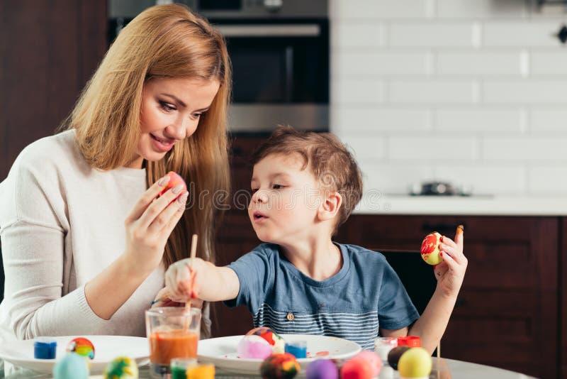 Madre joven feliz de Pascua y su pequeño hijo que pintan los huevos de Pascua fotografía de archivo libre de regalías