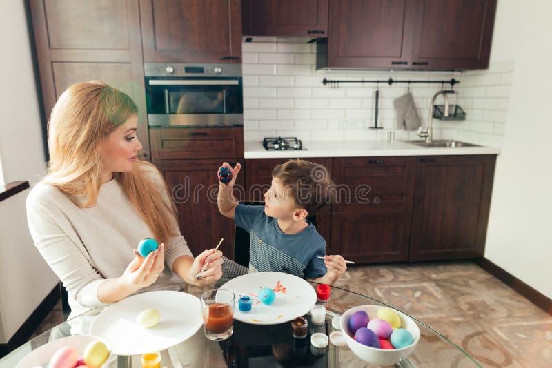 Madre joven feliz de Pascua y su pequeño hijo que pintan los huevos de Pascua foto de archivo