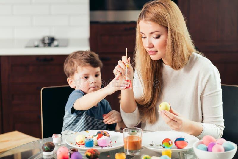 Madre joven feliz de Pascua y su pequeño hijo que pintan los huevos de Pascua imagen de archivo