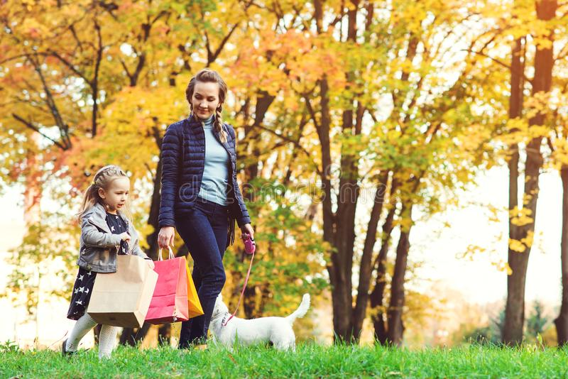 Madre joven feliz, pequeña hija con los bolsos de compras Compras del otoño, concepto de las ventas Mamá, hija y su perro caminan imagenes de archivo