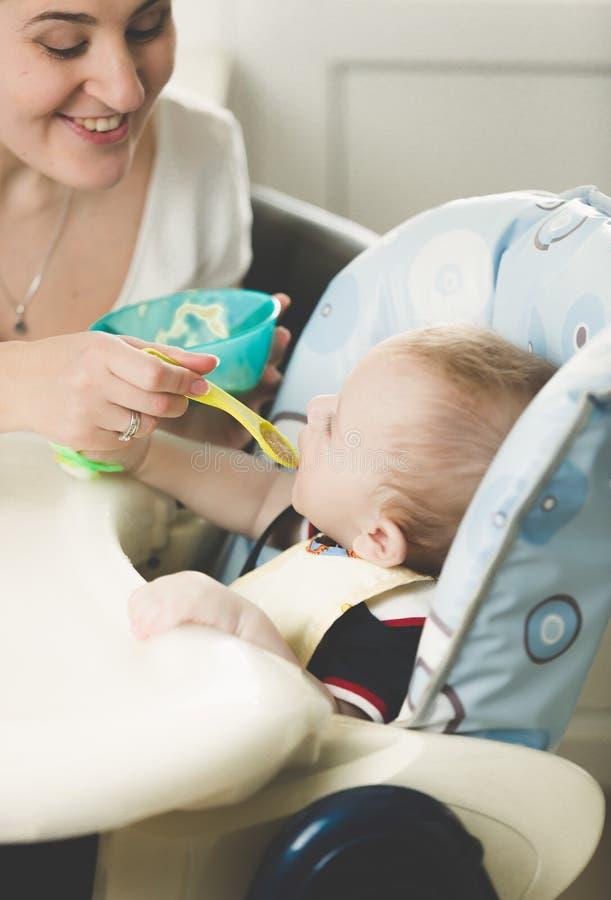 Madre joven feliz que alimenta a su bebé en highchair de la cuchara fotos de archivo libres de regalías