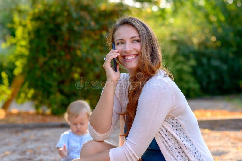 Madre joven feliz que charla en su móvil imágenes de archivo libres de regalías