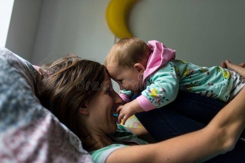 Madre joven feliz que juega con su hija del bebé imagen de archivo