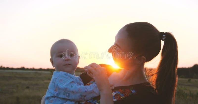 Madre joven feliz que juega con su niño en un campo en la puesta del sol fotos de archivo