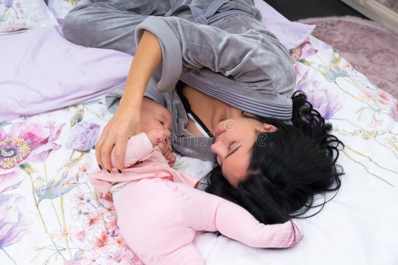 Madre joven feliz que juega con su pequeño bebé fotos de archivo