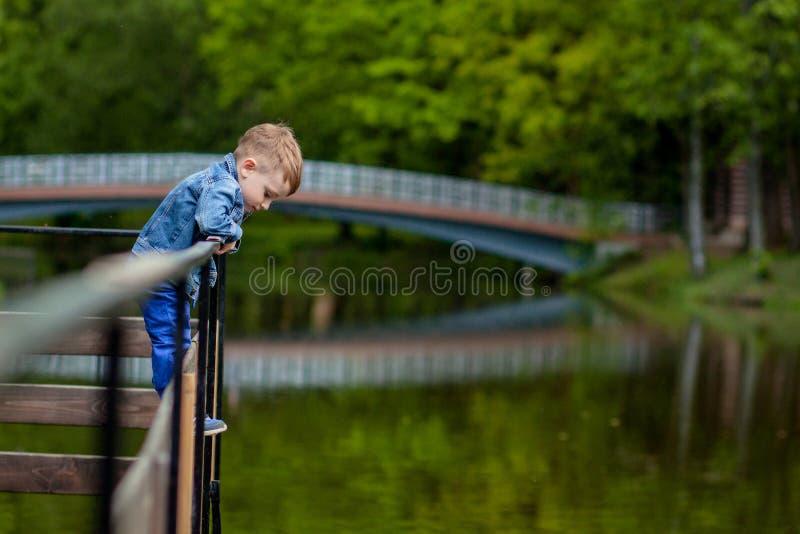 Madre joven feliz que juega y que se divierte con su peque?o hijo del beb? en d?a caliente de la primavera o de verano en el parq foto de archivo libre de regalías