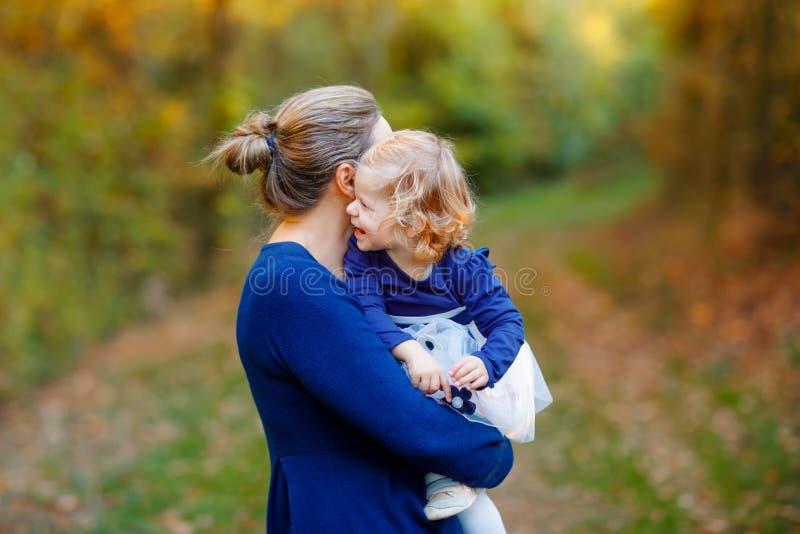 Madre joven feliz que tiene la hija linda del ni?o de la diversi?n, retrato de la familia junto Mujer con el beb? hermoso en natu fotos de archivo libres de regalías