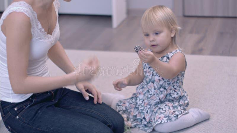 Madre joven feliz y su pequeña hija que exploran el joyero que se sienta en la alfombra imagen de archivo libre de regalías