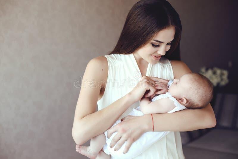 Madre joven hermosa con el pelo oscuro largo que presenta con su pequeño bebé adorable foto de archivo