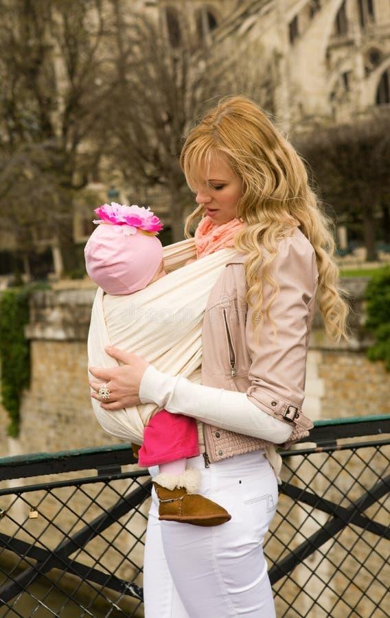 Madre joven hermosa con la hija del bebé en honda fotografía de archivo