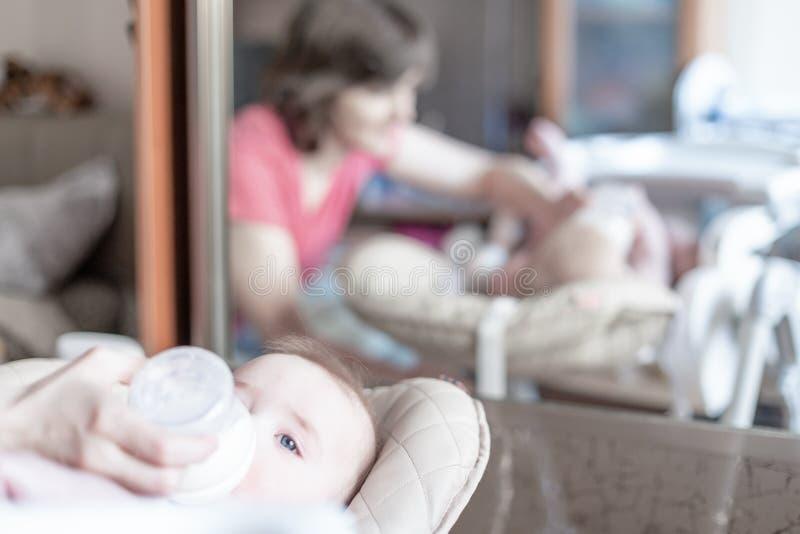 Madre joven hermosa que alimenta a su bebé de la botella foto de archivo