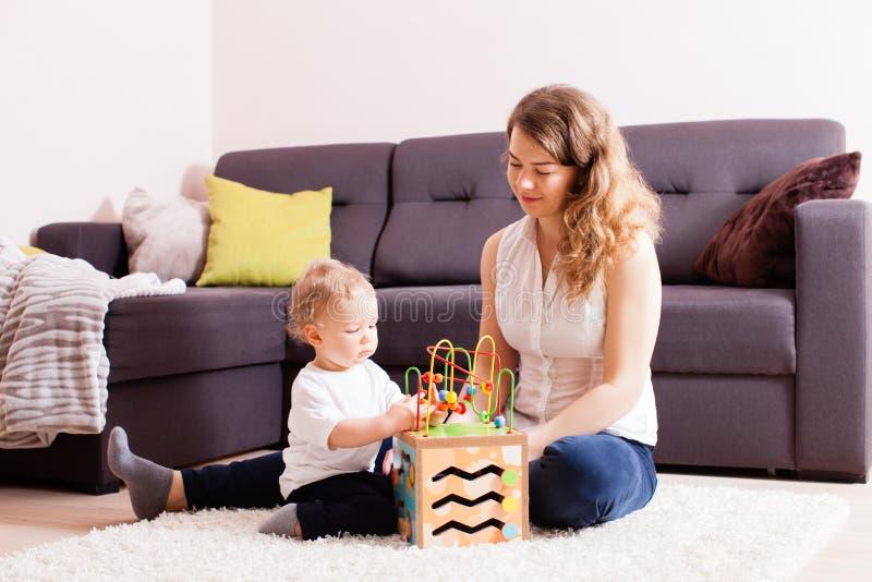 Madre joven hermosa que juega con su pequeño hijo en piso imagen de archivo libre de regalías