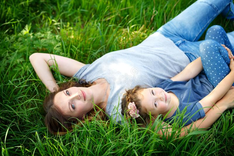 Madre joven hermosa y pequeña hija que mienten en hierba verde y la reclinación imágenes de archivo libres de regalías