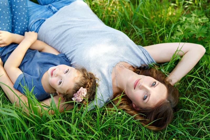 Madre joven hermosa y pequeña hija que mienten en hierba verde y la reclinación imagen de archivo libre de regalías