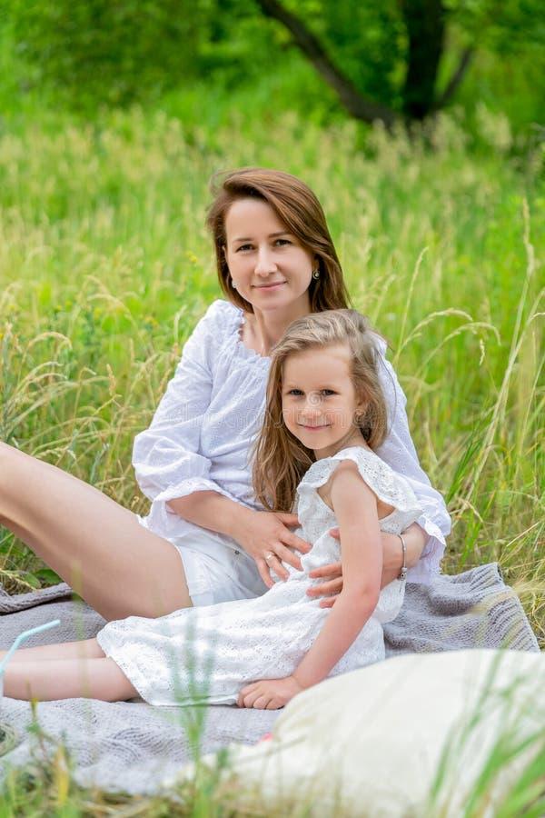 Madre joven hermosa y su pequeña hija en el vestido blanco que se divierte en una comida campestre Se están sentando en una tela  imagen de archivo