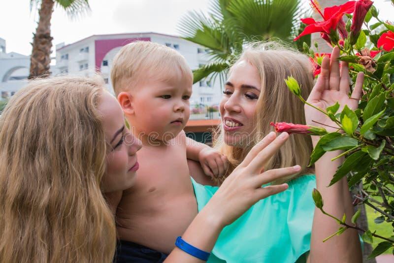 Madre joven, hija adulta e hijo joven en un parque foto de archivo
