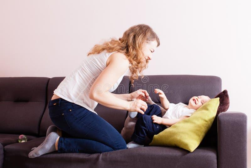 Madre joven loughing cosquilleando a su hijo adorable del niño en su sofá imagen de archivo libre de regalías