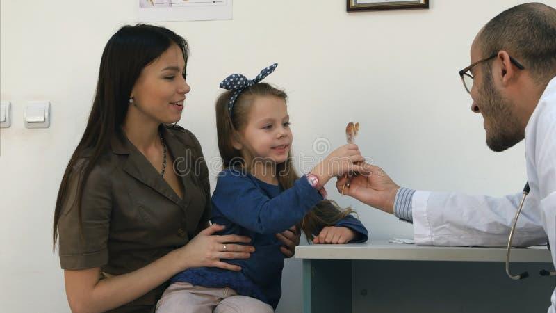 Madre joven orgullosa de su niña y doctor que le dan una piruleta después del examen fotografía de archivo